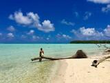 Beautiful young lady sitting on a palm tree in the turquoise lagoon of Marlon Brando's atoll Tetiaroa, Tahiti, French Polynesia