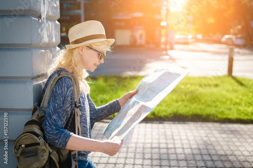 Woman tourist looking at the map in the old town. Poster