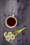 Dandelion flowers with a cup of tea on a wooden background