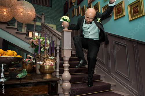 Poster young funny groom falls from ladders