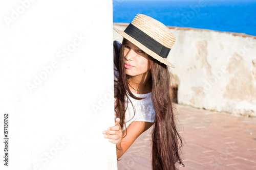 Poster Girl in straw hat peeks out from behind wall
