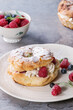 Homemade choux pastry cake Paris Brest with raspberries, almond, sugar powder, rosemary on white plate with berries over gray texture background. French dessert.