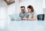 Two entrepreneurs sitting together working in an office desk - 157143511