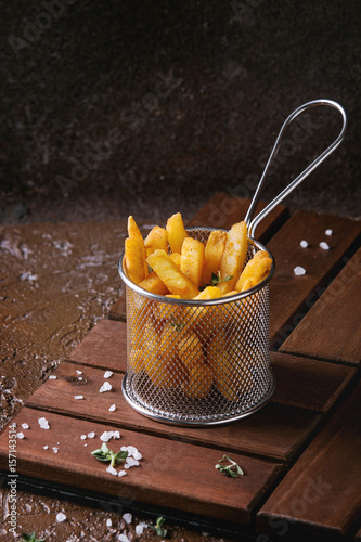 Poster Traditional french fries potatoes served in frying basket with salt, thyme on wooden board over brown texture background