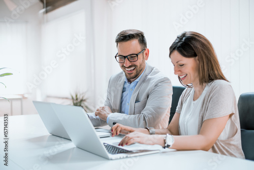 Two entrepreneurs sitting together working in an office Poster