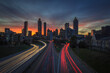 Long Exposure orange, pink, red, blue, purple sunset behind the Atlanta skyline from Jackson Street Bridge with streaked white and red car lights (company names have been edited out)