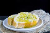 Rebanadas de pan mojadas en aceite de oliva virgen extra y romero espolvoreado - 157151374