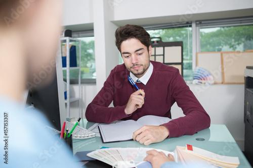 Men at desk pondering color samples