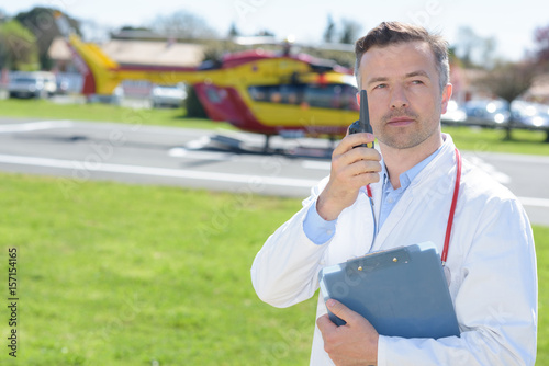 Doctor speaking into walkie talkie, air ambulance in background