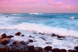 Beautiful pink tinted waves breaking on a rocky beach at sunrise on east coast of Big Island of Hawaii