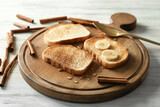 Wooden board with tasty cinnamon toasts on wooden table