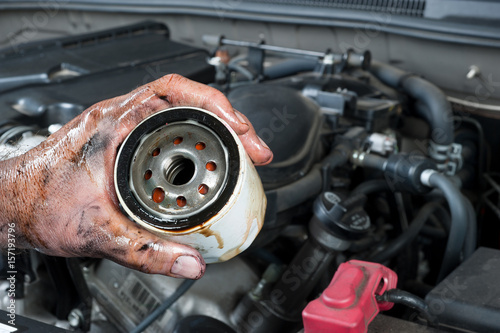 fototapeta na ścianę Auto mechanic holding oil filter