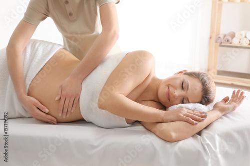 Leinwanddruck Bild Young beautiful pregnant woman having massage in spa salon