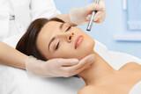 Fototapety Cosmetology. Spa clinic. Beautiful woman at facial treatment procedure. Young healthy skin. Facial mask. Skin rejuvenation.