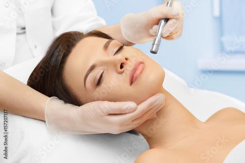 Fototapeta Cosmetology. Spa clinic. Beautiful woman at facial treatment procedure. Young healthy skin. Facial mask. Skin rejuvenation.