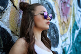 Beautiful girl dressed in a street style outfits posing in front of wall full of graffitis.