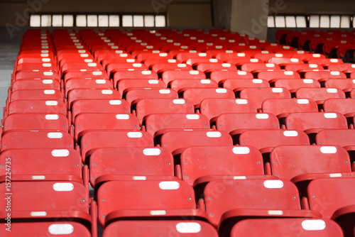 Red chairs in stadium Poster