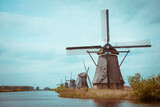 Traditional Dutch windmills on a canal bank in Nethelands vintage color toned