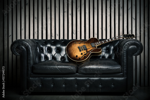 empty vintage sofa and electric guitar with modern wood wall recording studio background. Music concept with nobody