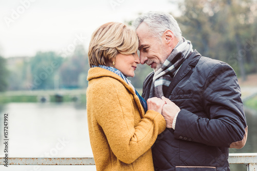Beautiful mature couple standing near lake