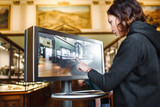 A woman in the museum uses the touchscreen monitor electronic guide, the concept of modern education - 157250361