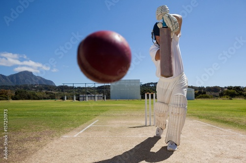 Full length of batsman playing cricket on pitch against blue sky