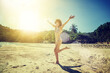 Beautiful young woman with long hair runs along a tropical beach. Happiness, joy, vacation and travel concept