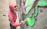 Fototapeta Młodzieżowe - Street artist painting colorful graffiti on generic wall - Modern art concept with urban guy performing and preparing live murales with green aerosol color spray - Sunny afternoon neutral filter © Mirko