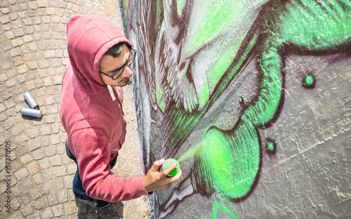 Street artist painting colorful graffiti on generic wall - Modern art concept with urban guy performing and preparing live murales with green aerosol color spray - Sunny afternoon neutral filter - 157270505