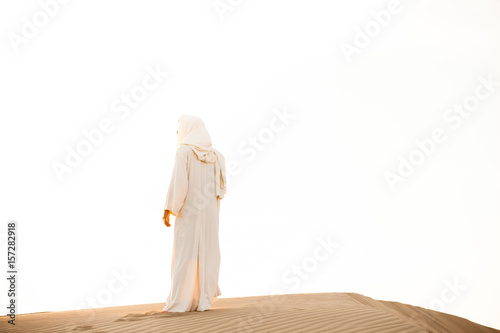 Jesus Christ watches the sunset while standing on top of a pile of sand in the sand dunes.