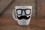 Coffee mug with mustache and eyeglasses on table