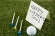 Fathers day message with golf ball and tee on grassy field