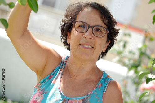 Portrait of a mature brunette woman with eyeglasses, outdoor Poster