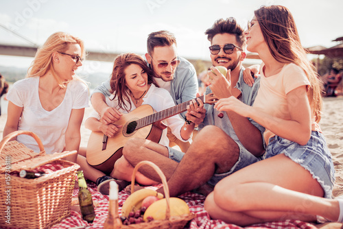 Happy young friends relaxing and playing guitar at the beach