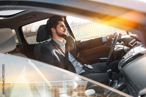 Plakat Handsome businessman driving  car secured with  seat belt.