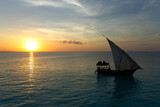 Stunning sunset captured north on Zanzibar, Tanzania, Africa. Sailboat passing by.