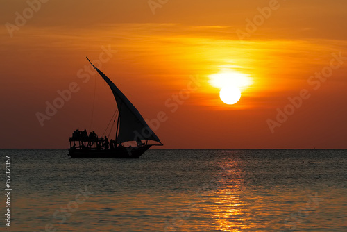 Canvas Zanzibar Stunning sunset captured north on Zanzibar, Tanzania, Africa. Sailboat passing by.