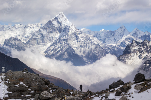 Ama Dablam mountain, sky, clouds, and hiker. Himalaya.