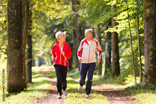 Poster Jogging Senior Couple doing sport outdoors, jogging on a forest road in the autumn