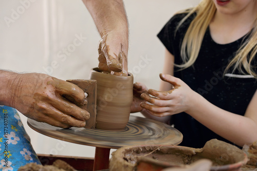 Child in clay studio working on a bowl. Potter sculpting clay pot on a turning pottery wheel