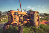 old Tractor parked on meadow against blue sky.