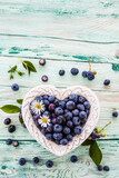 Tasty and fresh forest blueberries in a heart shaped bowl on wooden table with space for text.