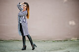 Fashionable woman look with black and white striped suit jacket, leather pants posing against wall. Concept of fashion girl.