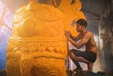 man in traditional Ancient style costume with engraving Tool create the candle sculpture for the important day of Buddhism in Thailand