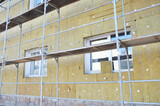 Install Rock Mineral Wool Insulation. Energy efficiency house wall  renovation for energy saving. Exterior house wall heat insulation with mineral wool, building under construction. - 157380390