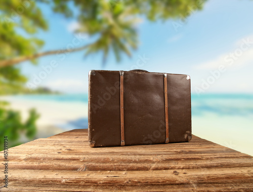 Poster Retro luggage placed on wooden planks with tropical beach on background