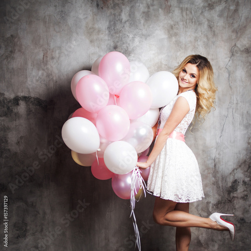 Charming young blonde in a white dress with pink sash, holding a large bundle of balloons Poster