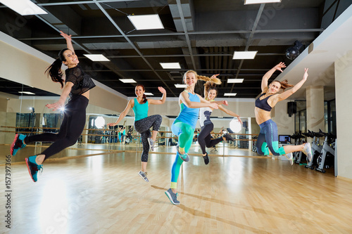 Póster A group of girls jump with smiles in the gym.