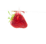 Throw the strawberries into water on white background