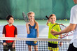Leinwanddruck Bild - Joyful pupils learning to play tennis